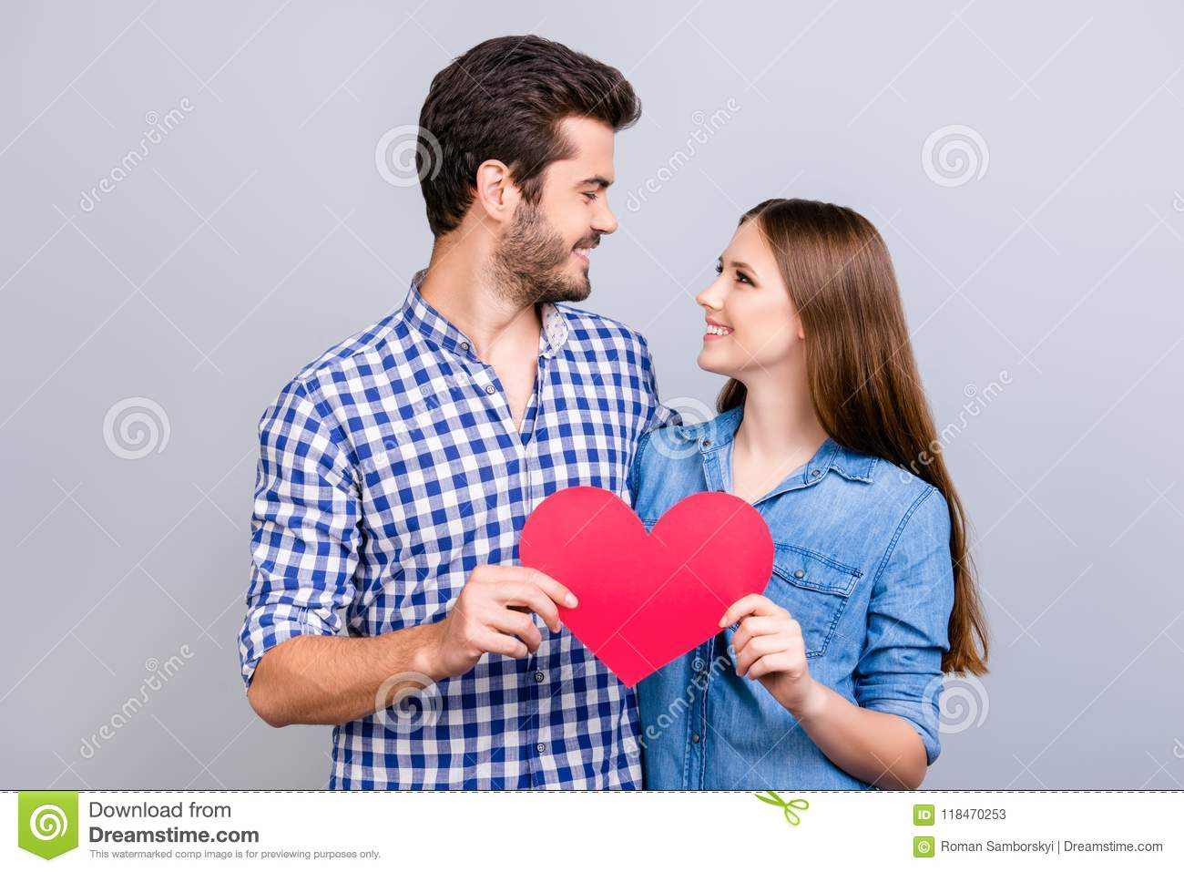 Love story. Trust and feelings, emotions and joy. Happy young lovely couple in love is posing, wearing casual shirts, holding big