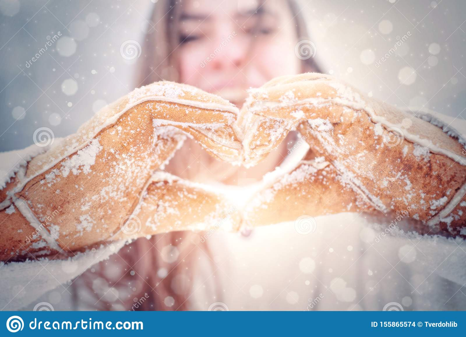 Love winter. Happy woman shows heart. Woman hands in winter gloves Heart symbol shaped Lifestyle and Feelings concept