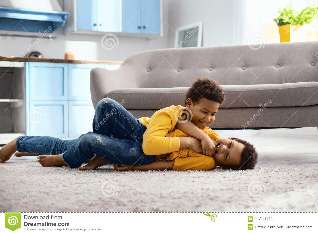 Cheerful little boy tickling his younger brother on floor