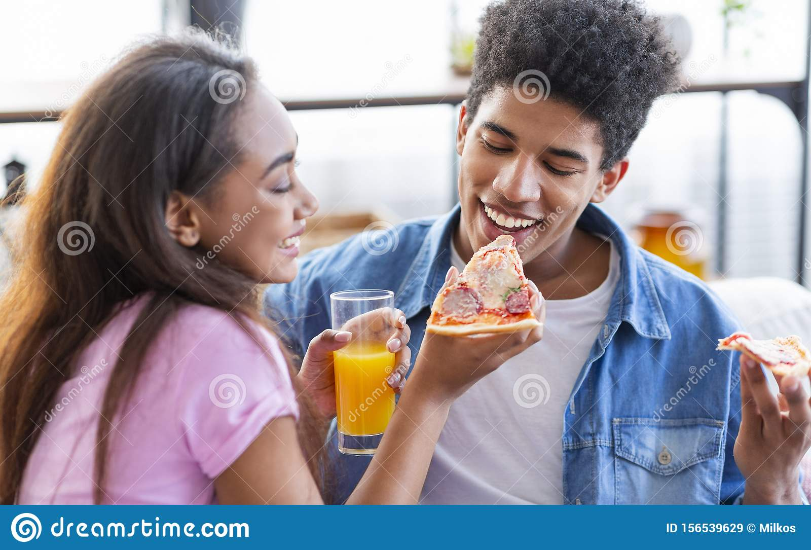 Lovely African American Couple Sharing Pizza On Date At