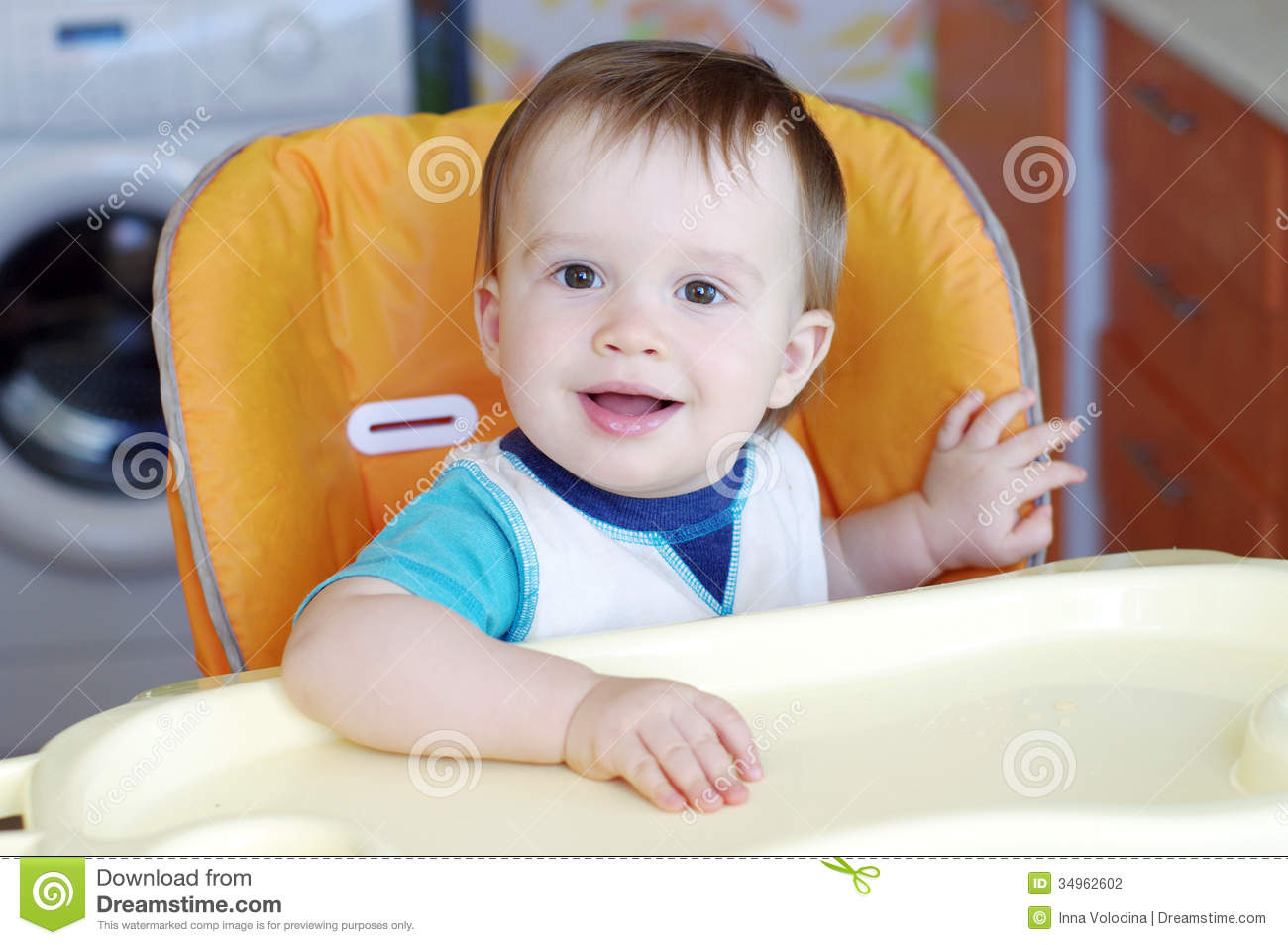 Lovely baby sitting on baby chair on kitchen stock photo for Toddler sitting chair