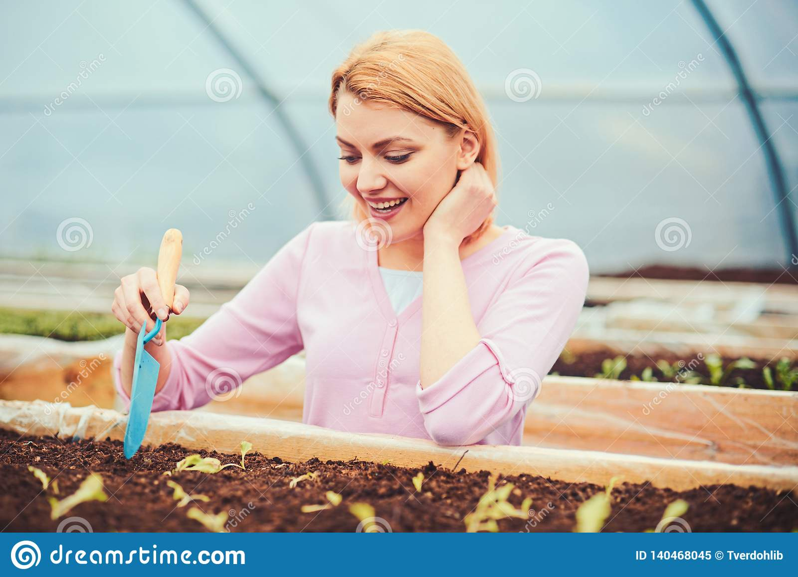Lovely Blond Lady Digging Small Hole In Plant Box. Female