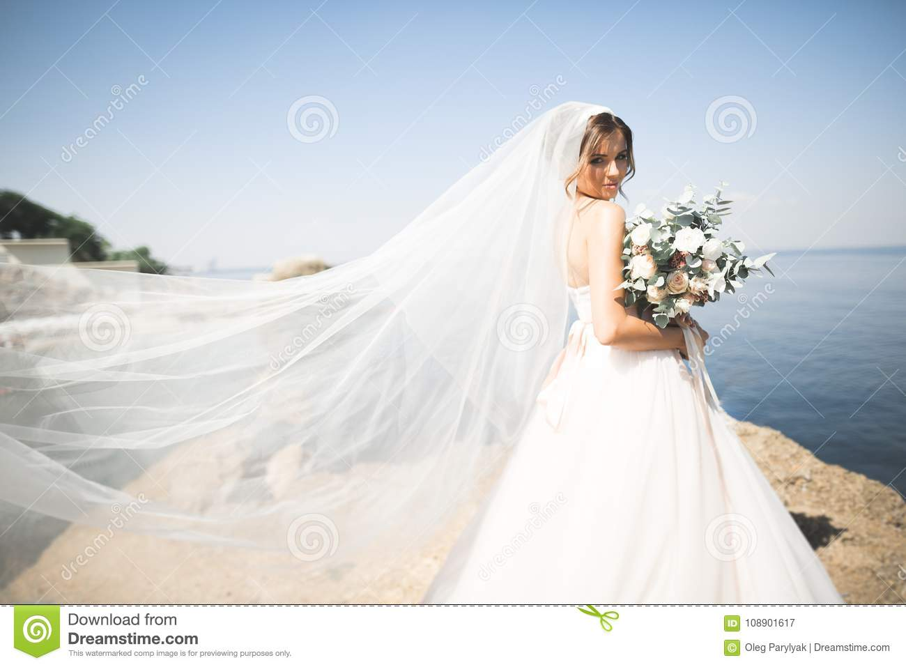 Lovely Bride In White Wedding Dress Posing Near The Sea With ...