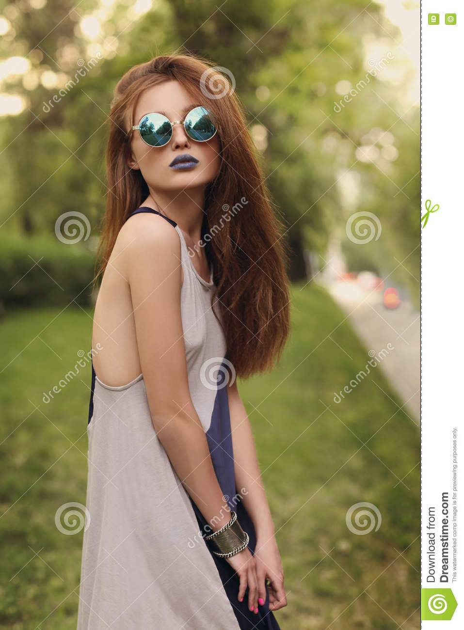 Lovely brunette girl with blue lips in round sunglasses