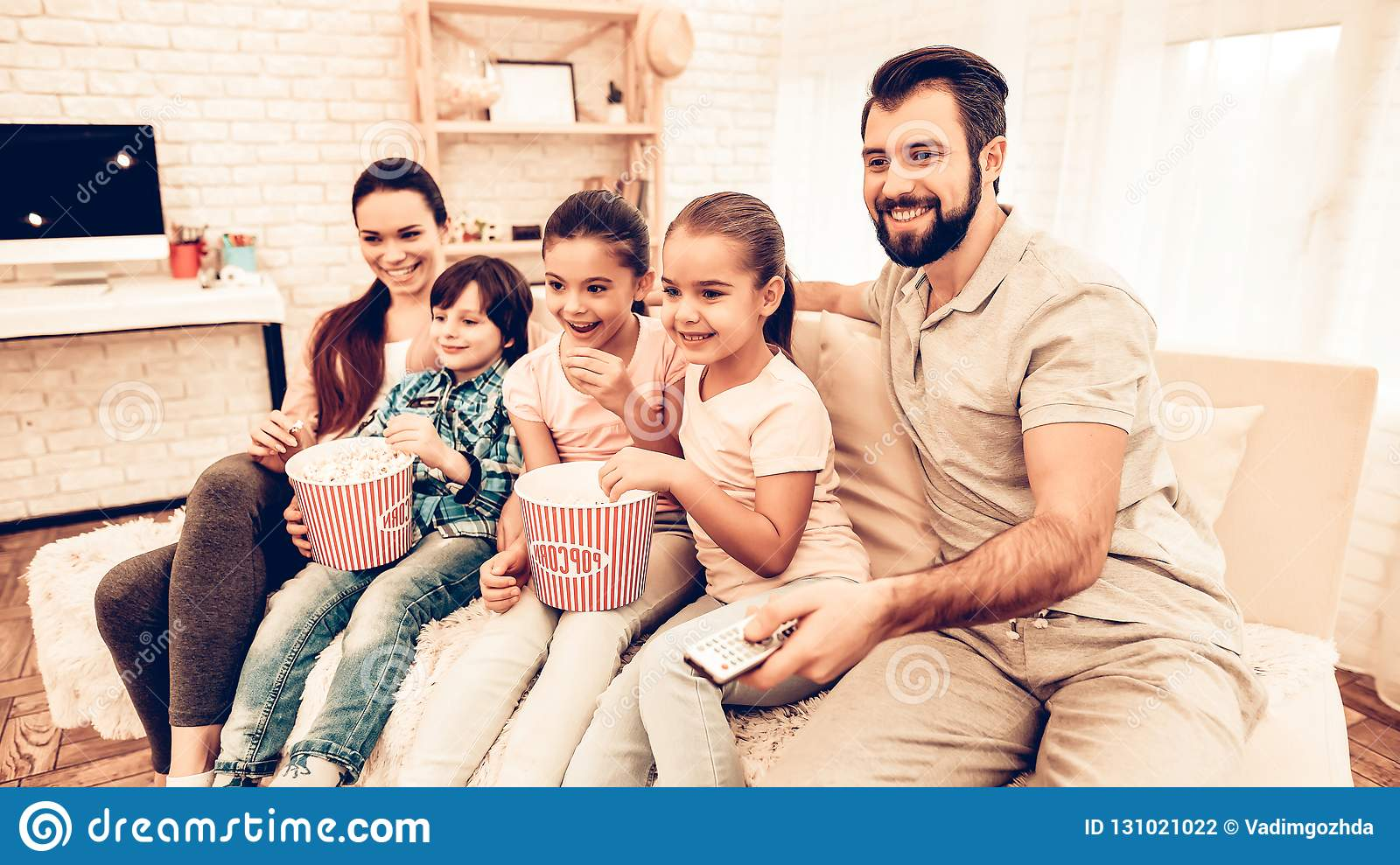 Lovely Cheerful Family Watching Movie at Home