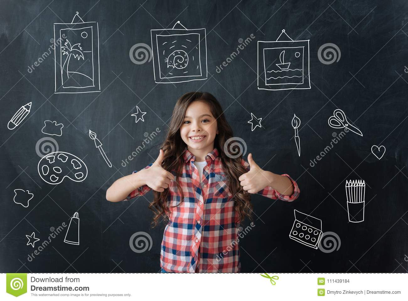 Lovely child feeling happy while showing her drawings