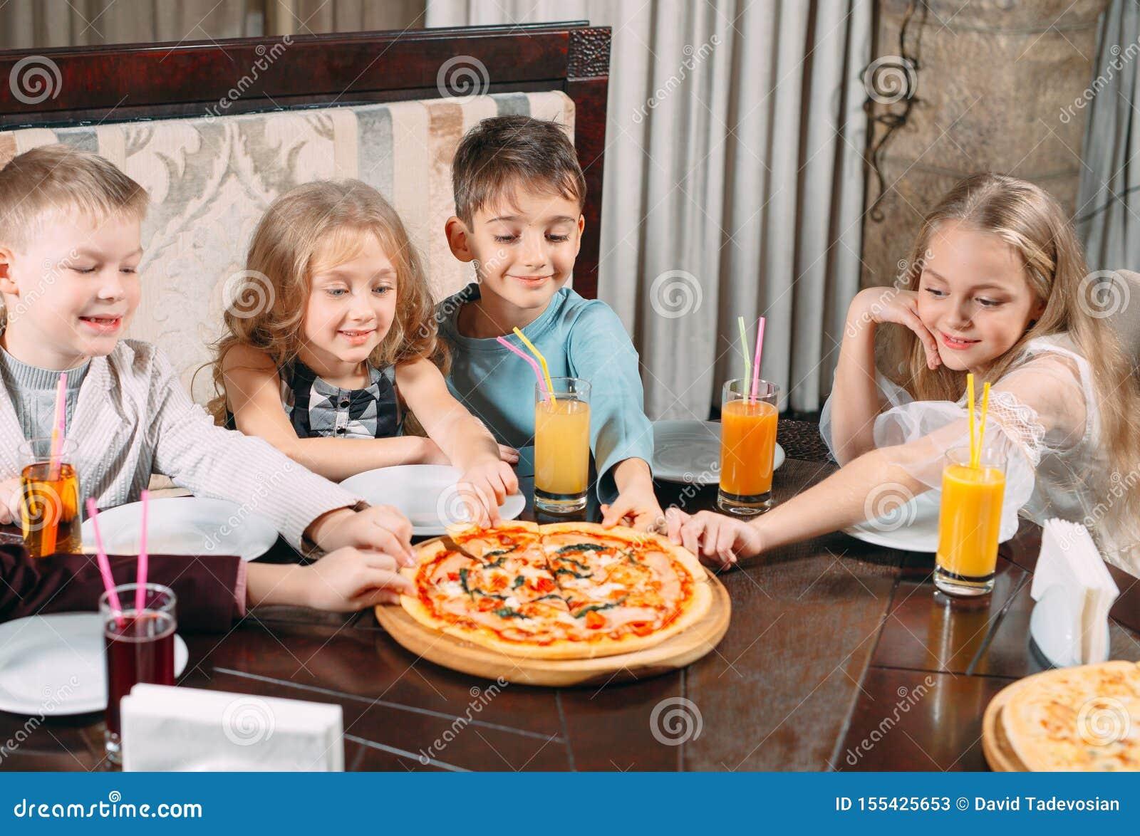 Lovely children eat pizza in the restaurant