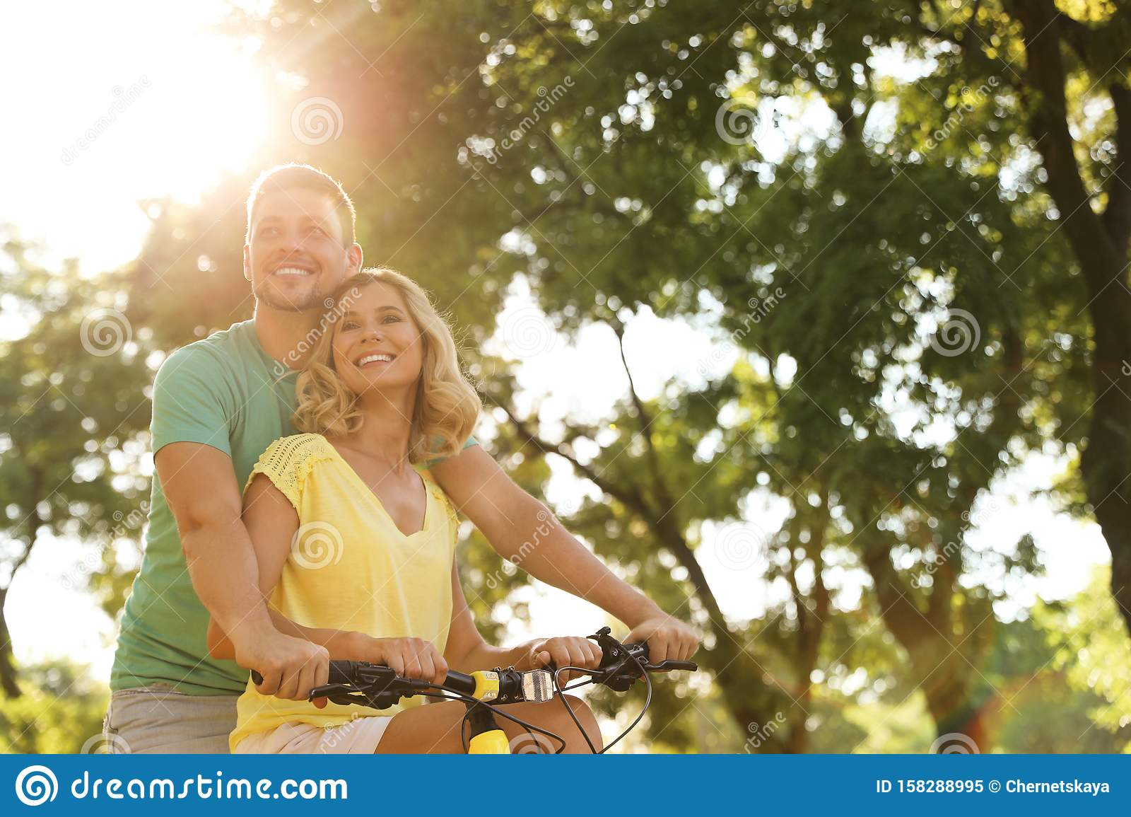 Lovely couple with bicycle in park