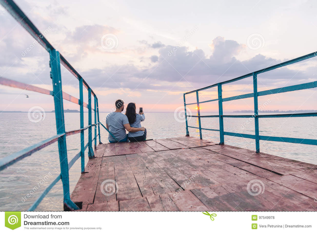 Lovely couple sitting on the pier and looking on sunrise