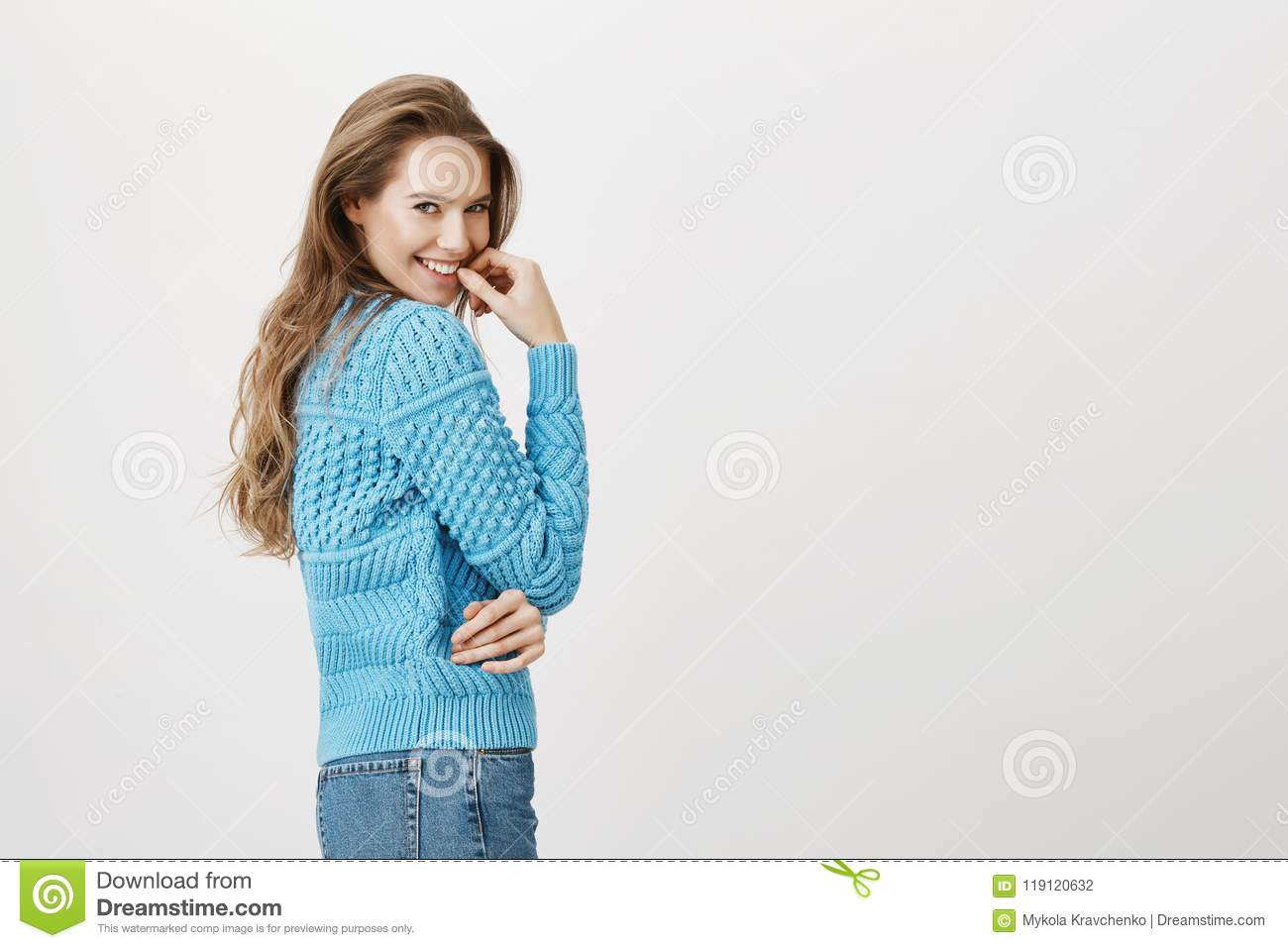 Lovely european adult woman standing in profile while turning at camera, smiling and holding finger near lip with