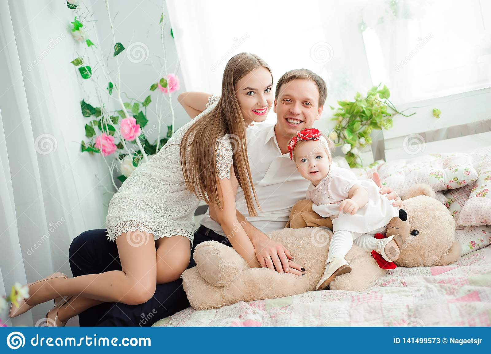Lovely family smiling and laughing, posing at camera, and hugging each other for family photo.