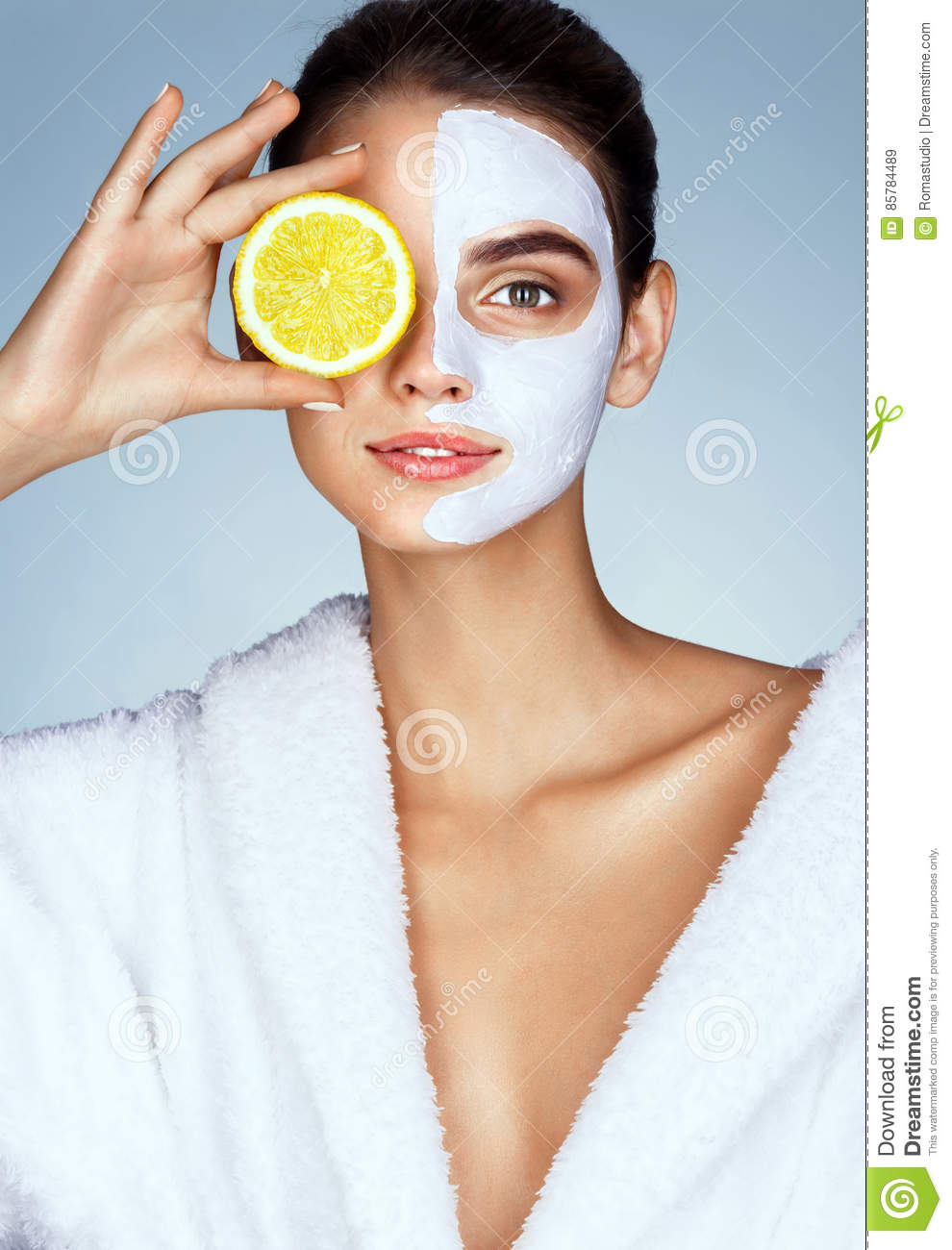 Lovely girl holding a slice of lemon in front of her face and smiling.