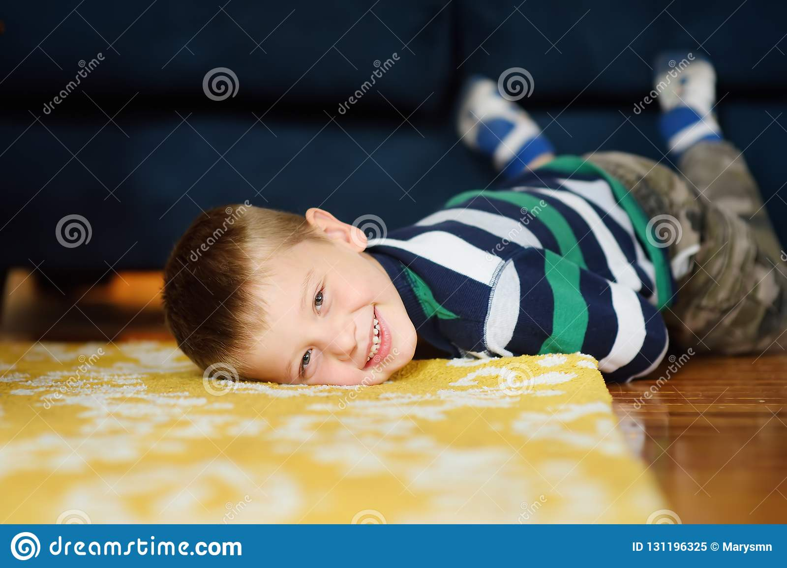 Lovely Little Boy In Striped Jumper Laying On The Floor In The