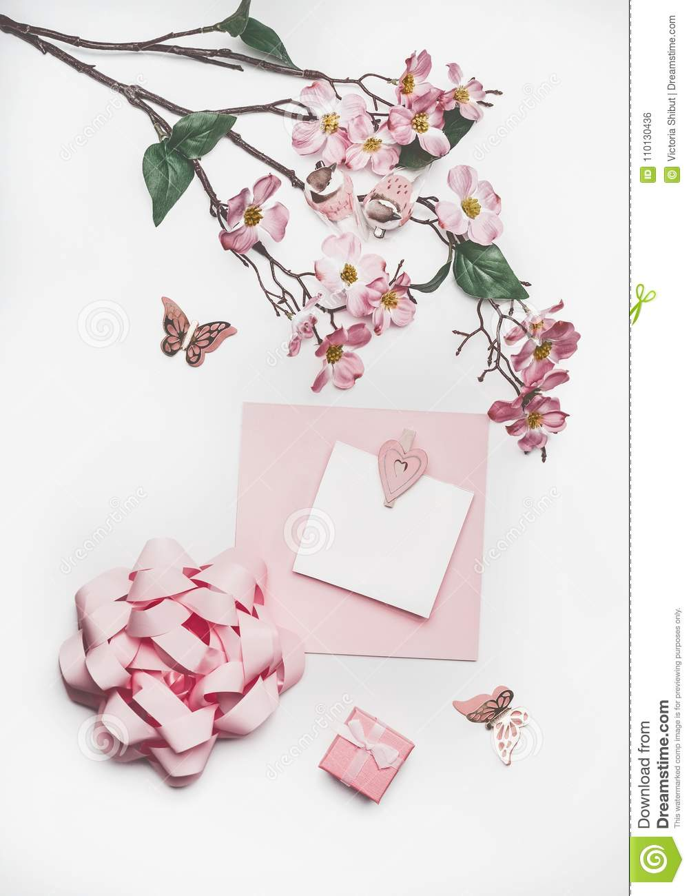 Lovely pastel pink greeting card mock up with blossom decoration, hearts, little gift box and bow on white desk background, top vi