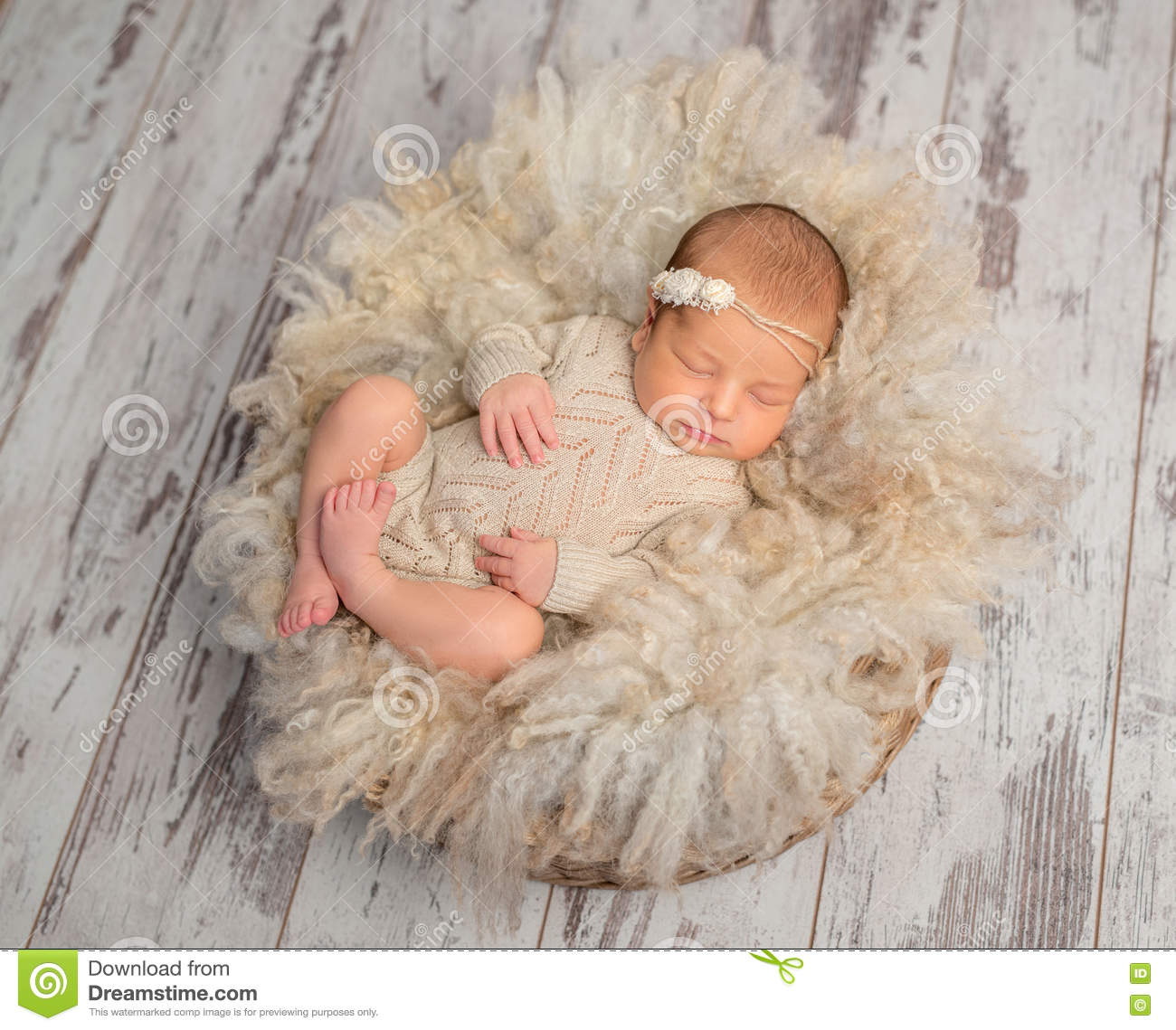 lovely sleeping newborn baby in knitted jumpsuit in basket stock