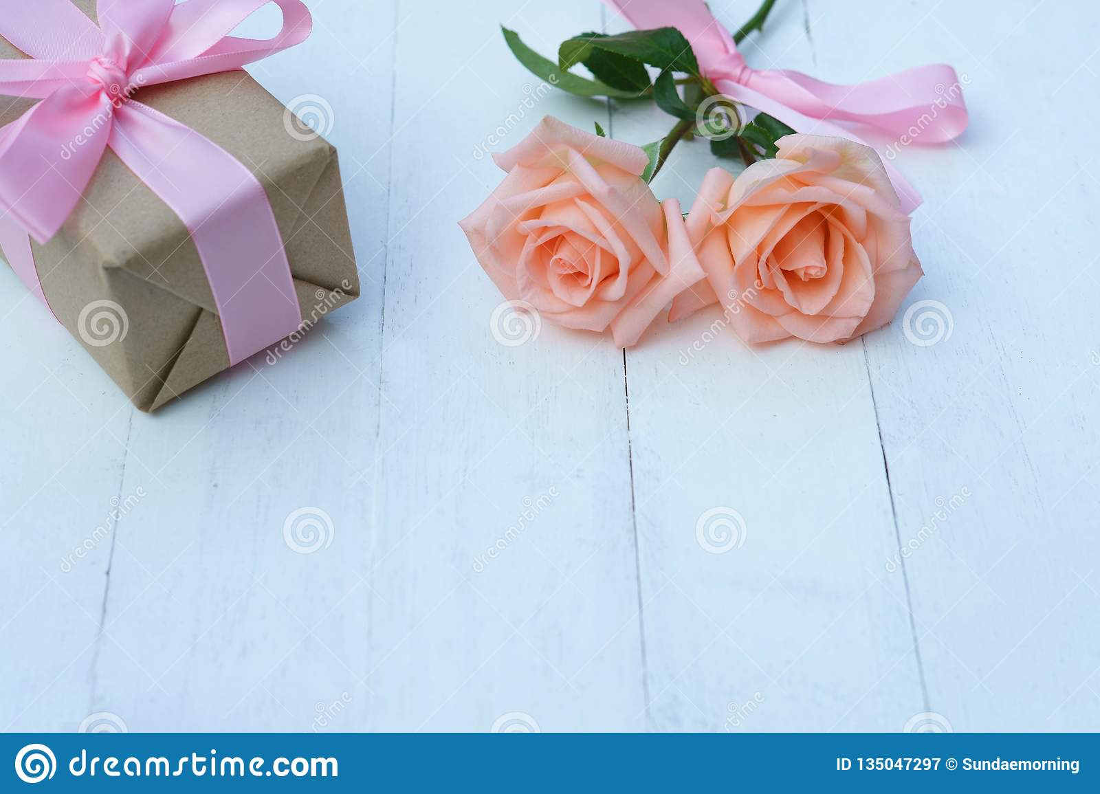 Lovely soft orange pink color rose tied by pink ribbon and brown gift box on white wood table background, sweet valentine present