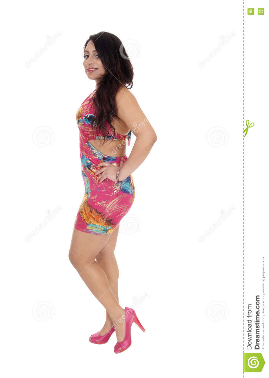 7fb04890624 A beautiful young East Indian woman in a colorful summer dress standing in  profile in high heels isolated for white background.
