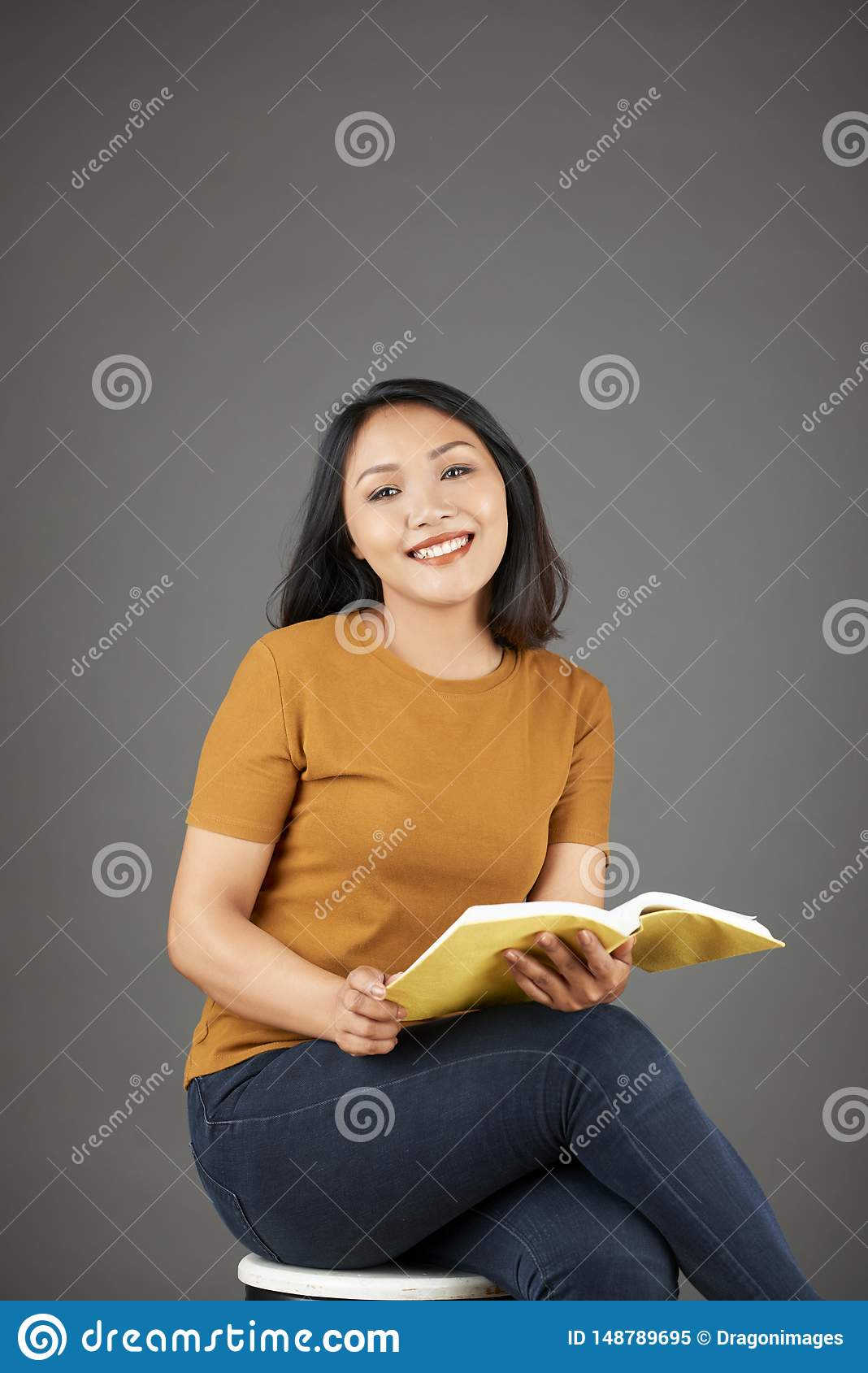 Lovely young Asian woman reading