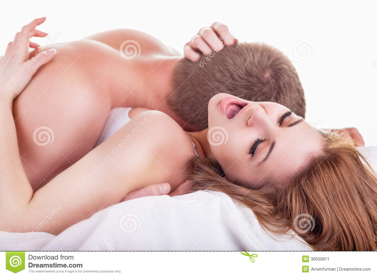 Young Beautiful Amorous Couple Making Love In Bed On White Background