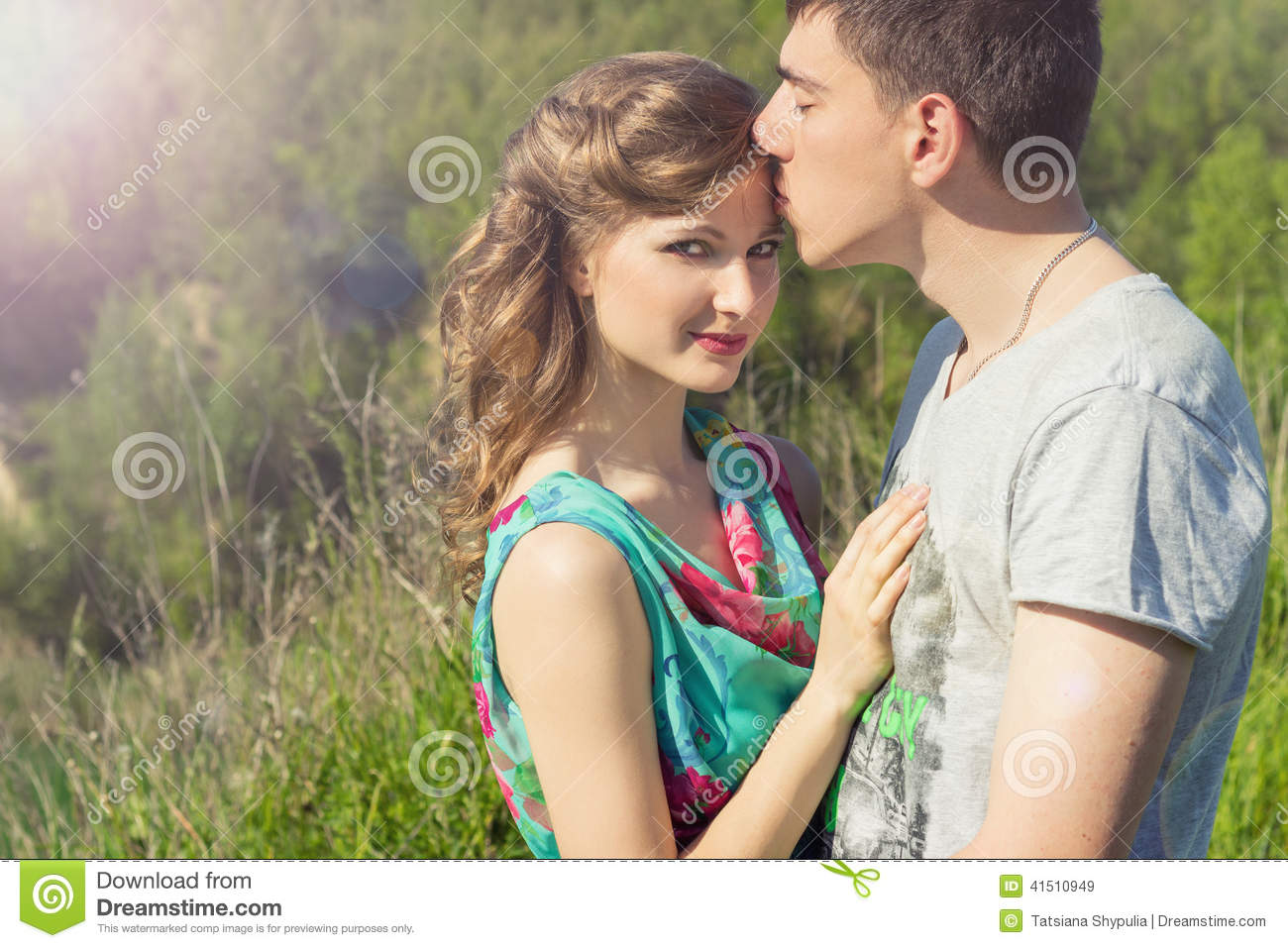 Loving beautiful couple of guys and girls in the field walking man kissing the girls forehead