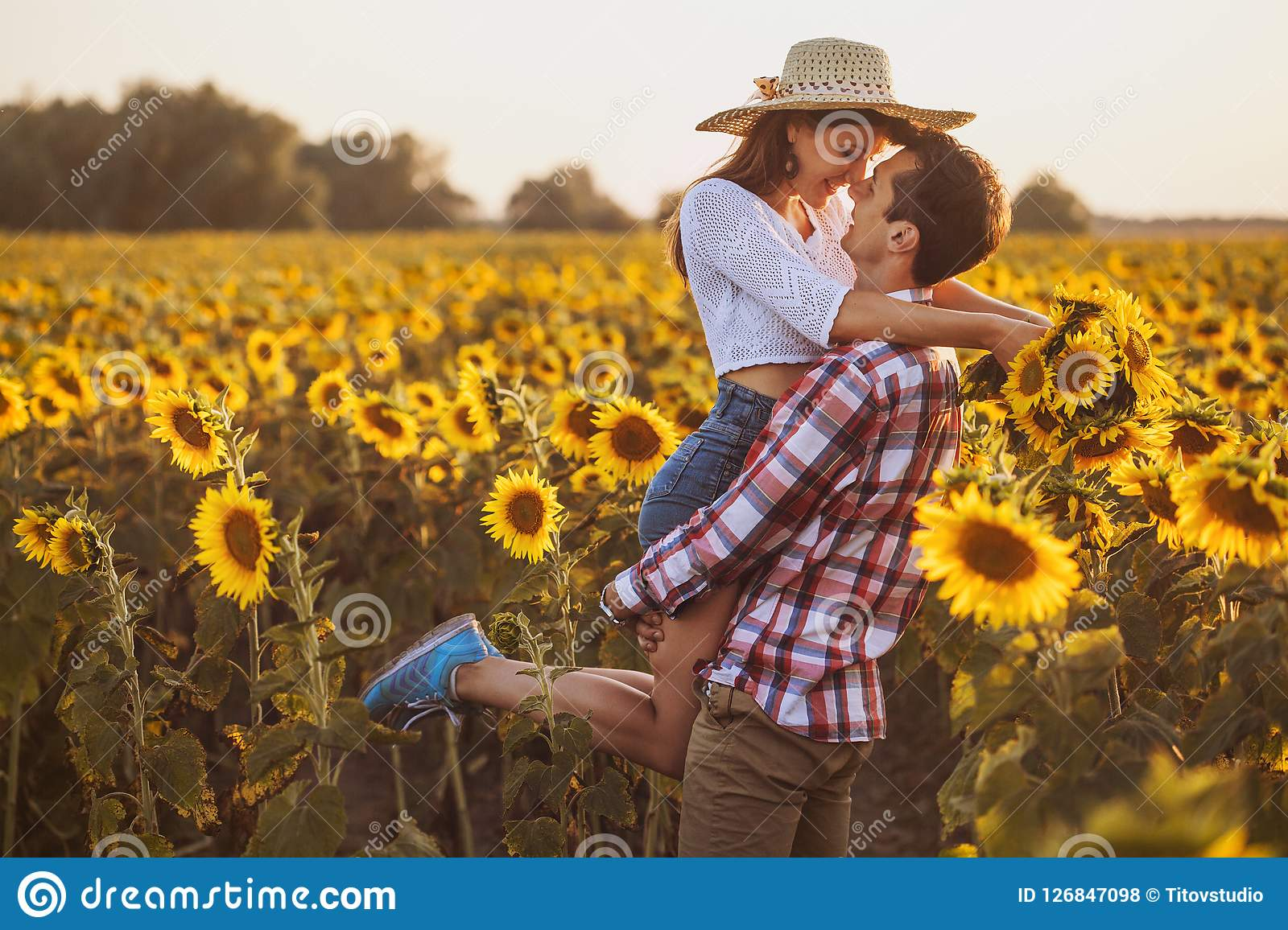 Loving couple in a blooming sunflower field