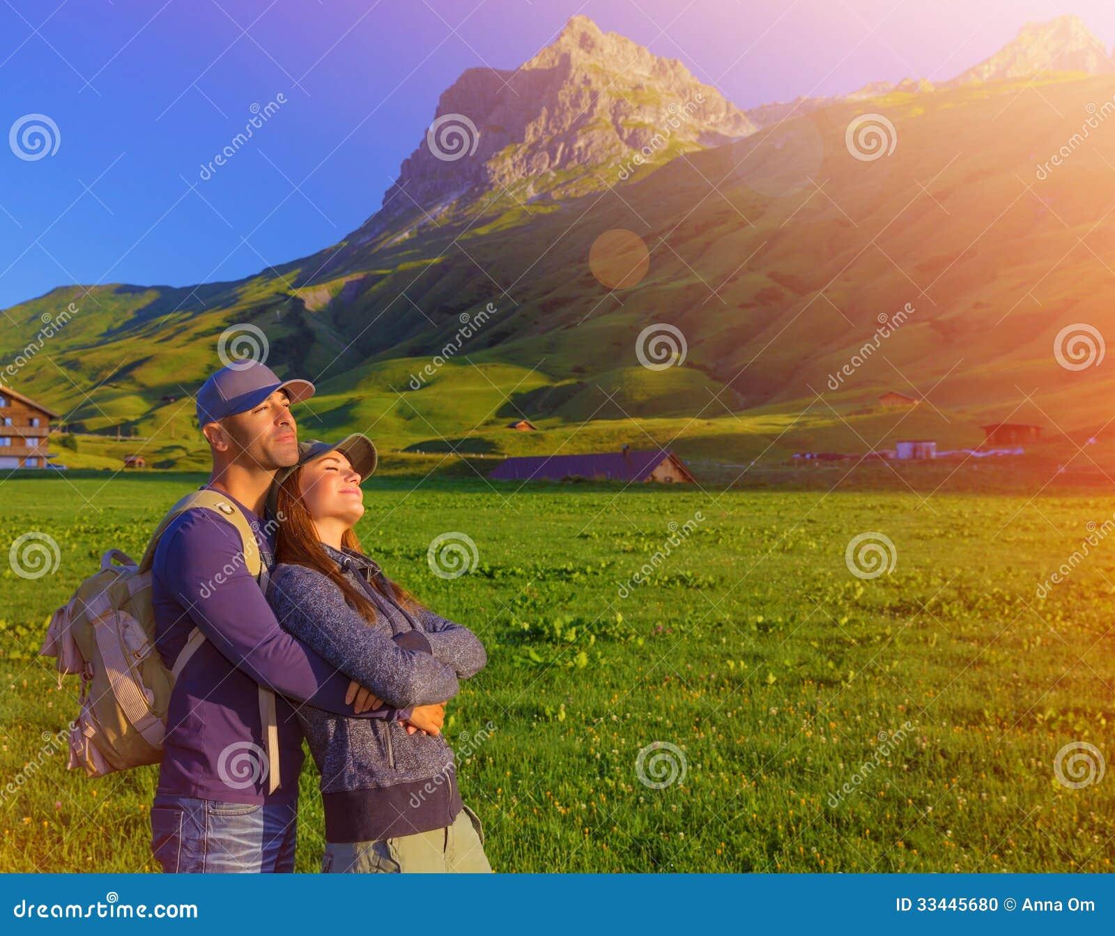 Couple Enjoying Their Summer Holidays Stock Photo: Loving Couple Enjoying Sunset In The Mountains Stock Photo