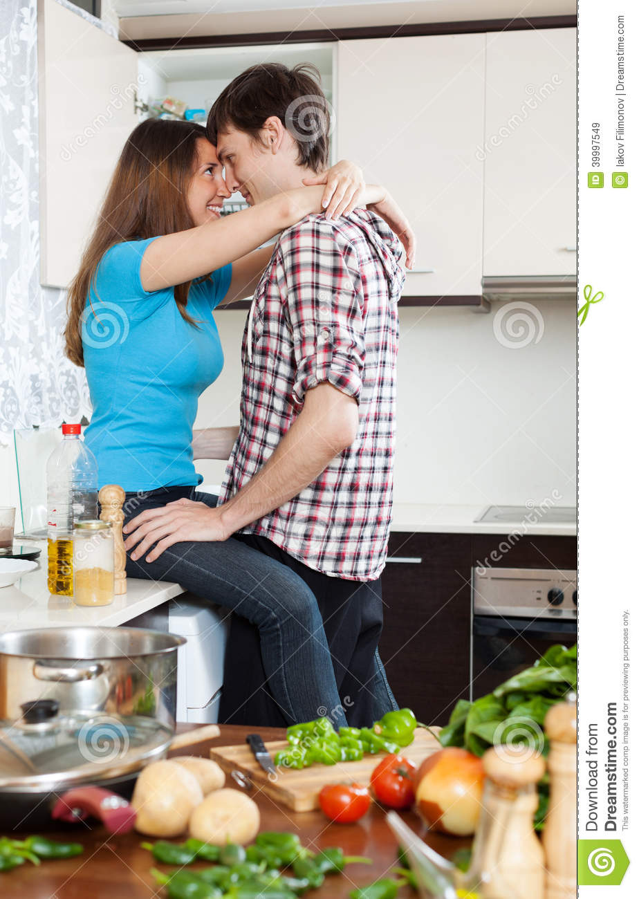 Loving Couple Having At Table In Kitchen Stock