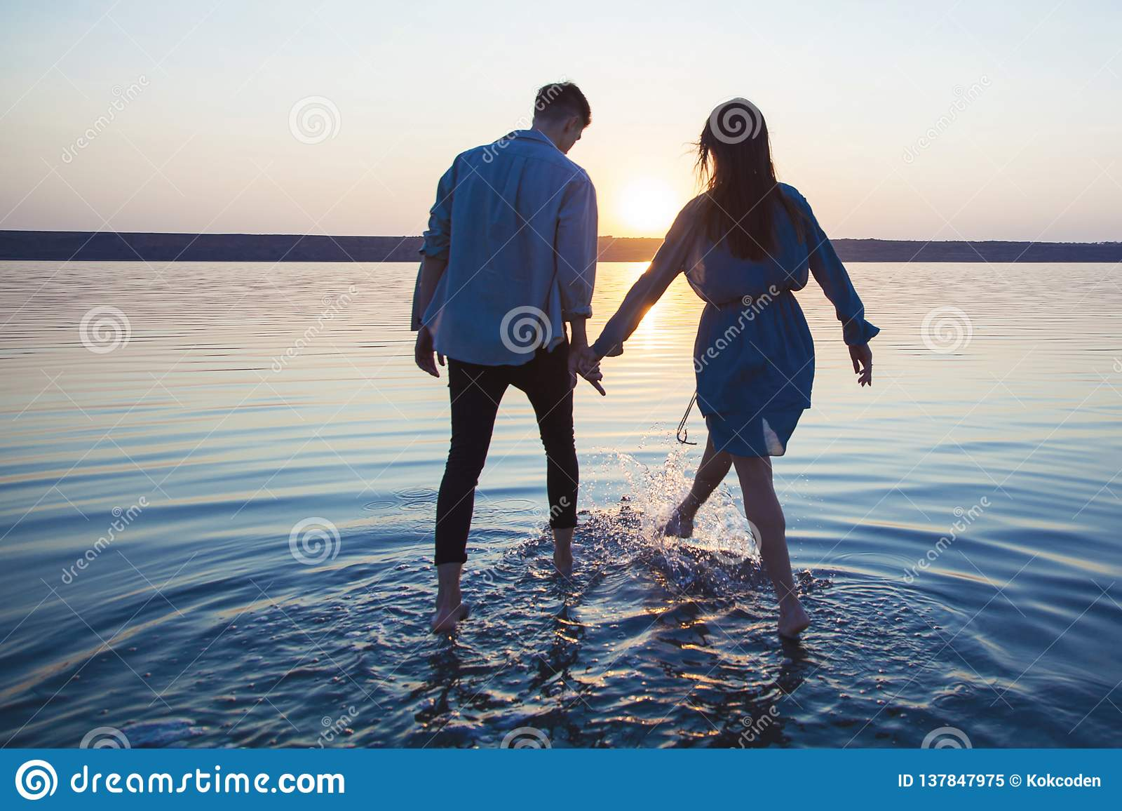 A loving couple holding hands is on the water.