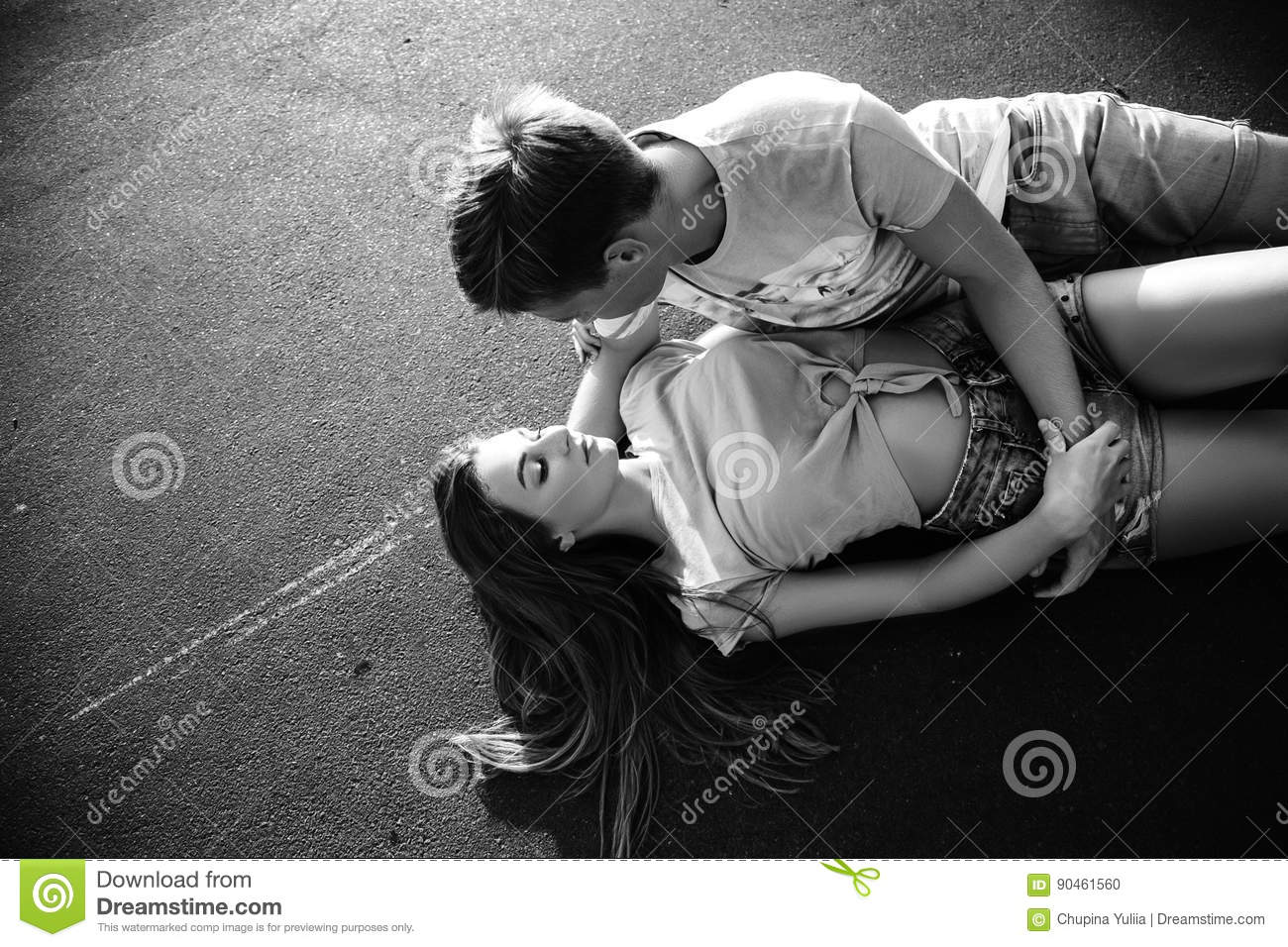 Beautiful sweet couple lying on the asphalt and hugging on the street during sunset black and white