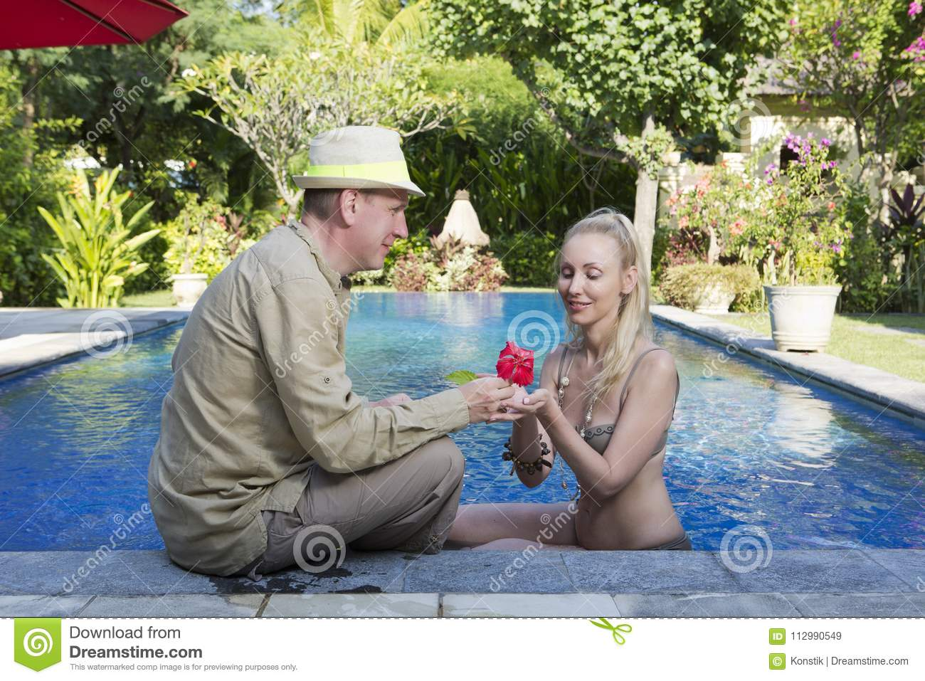 Loving couple in the pool in a garden with tropical trees. The man embraces the woman