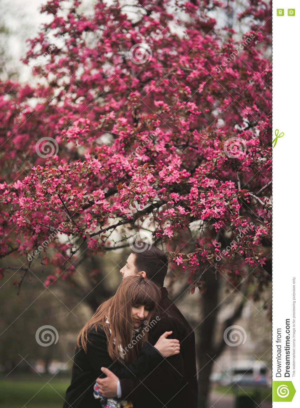 Loving couple under a tree with flower in the park