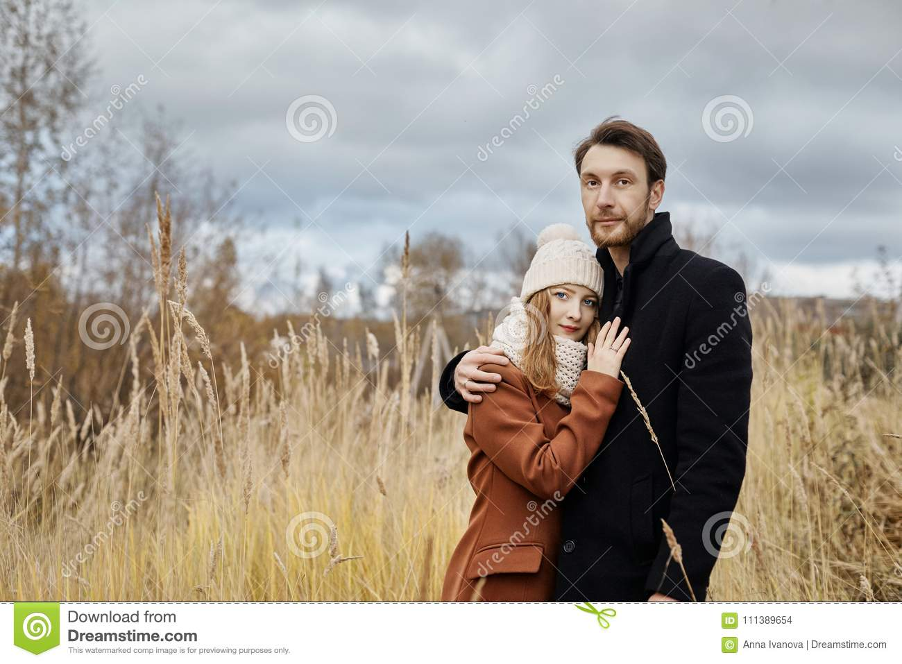 Loving couple walks in the autumn Park, hugs and kisses. Woman i