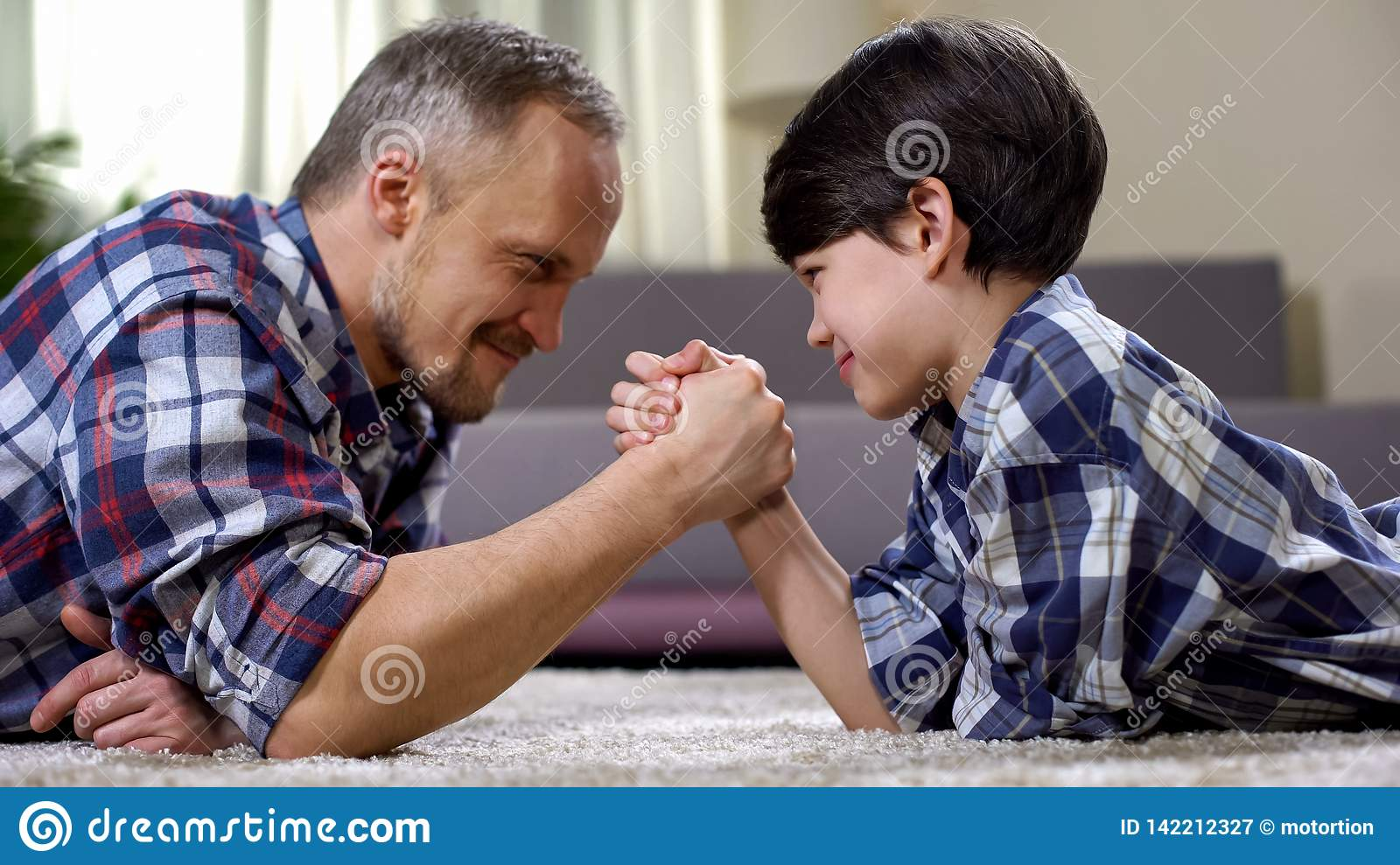 Loving father and kid arm wrestling on the floor, weekend leisure at home, fun