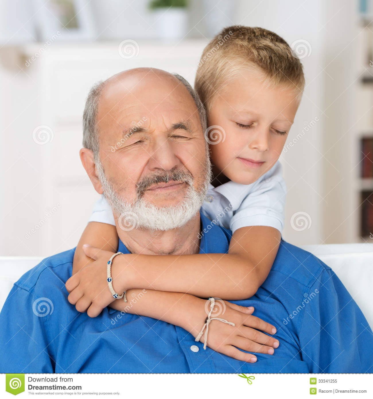 ... young grandson hugs him from behind with his arms around his neck