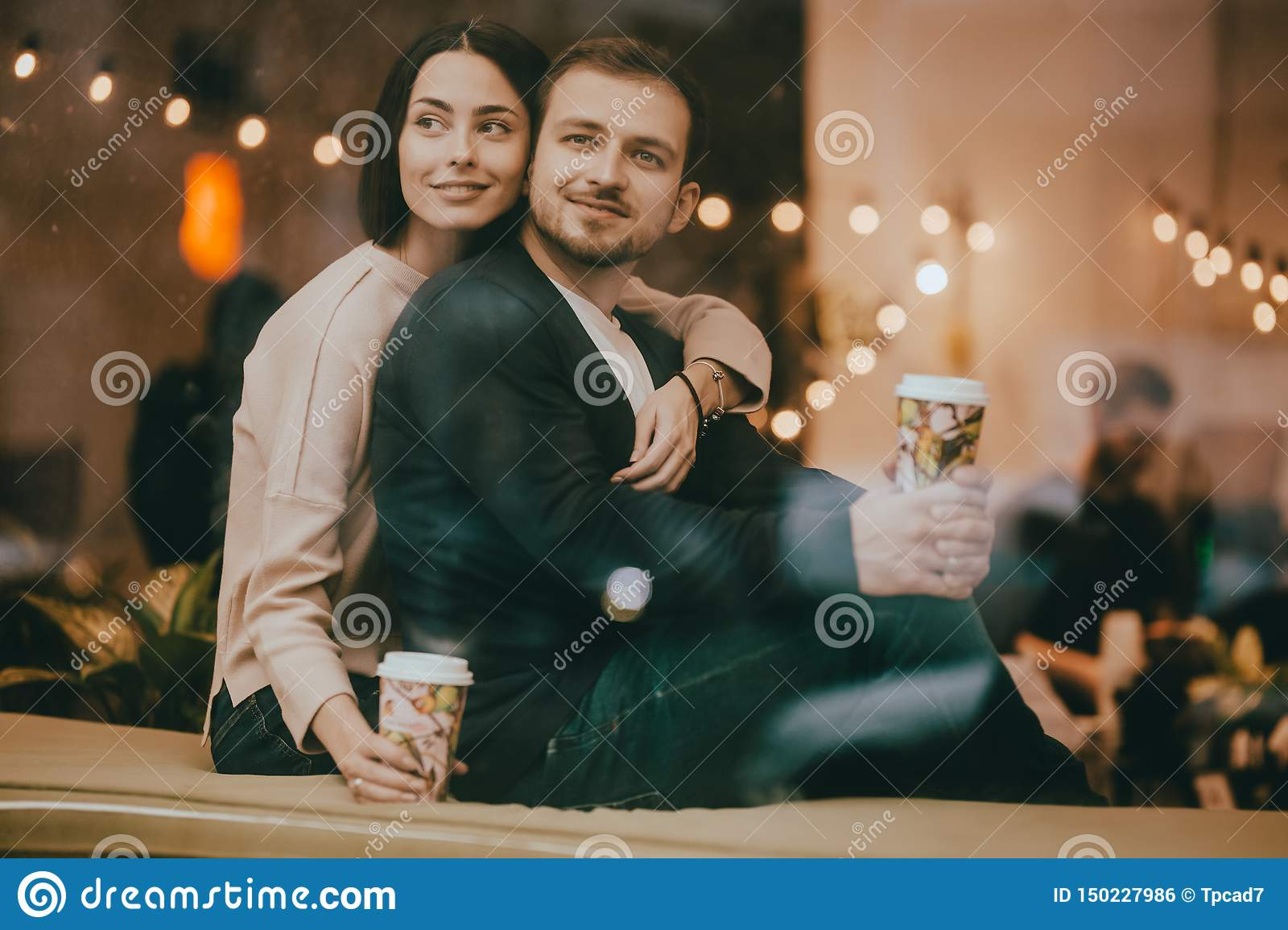 Loving guy and girl sit hugging on the windowsill in a romantic cafe