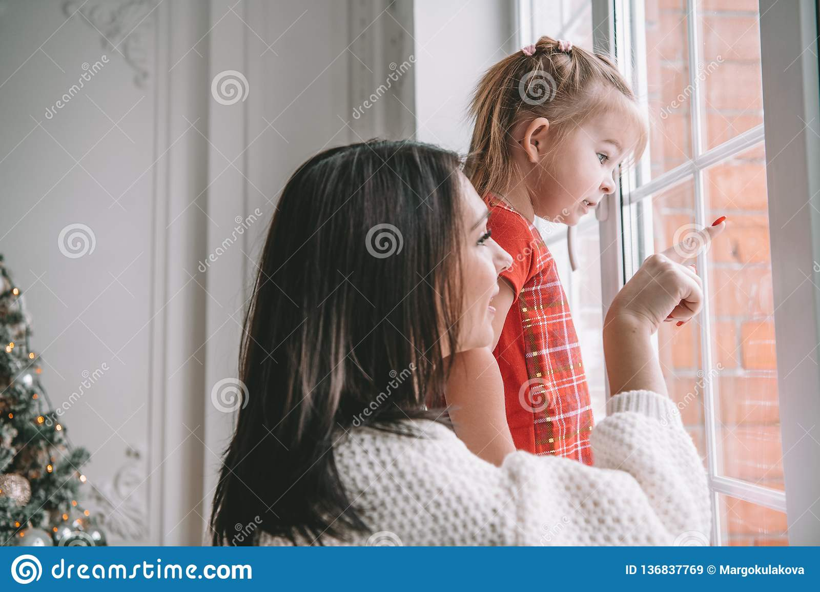 Loving mother playing with her baby girl looking at the window