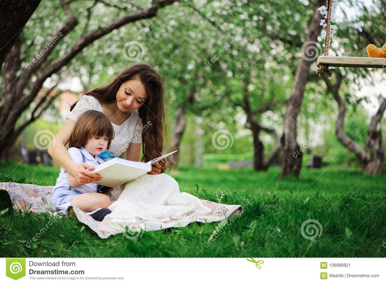 Loving mother reading book to toddler son outdoor on picnic in spring or summer park. Happy family and mothers day