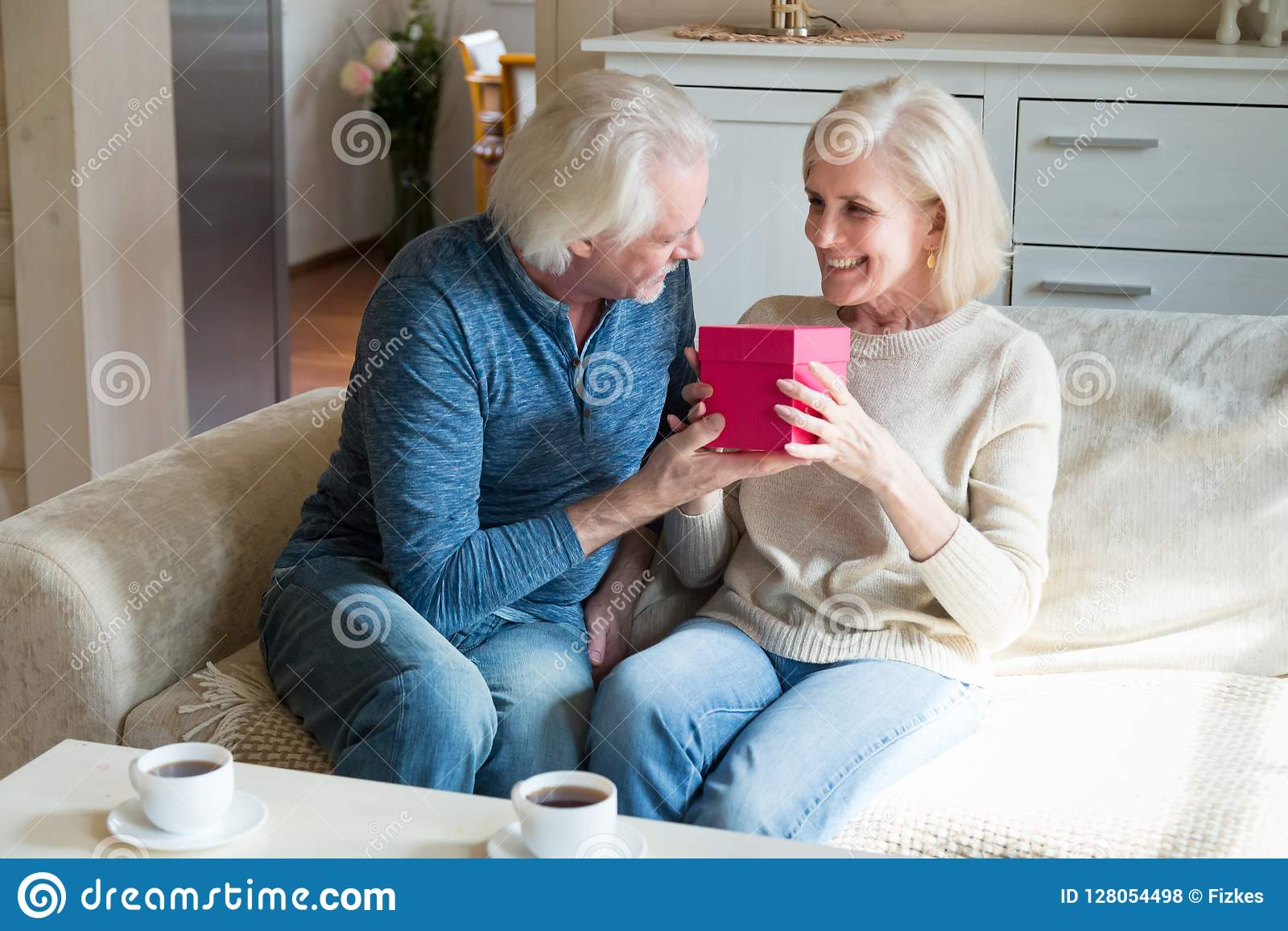 Loving Senior Husband Presenting Romantic Gift Box To Mature Wif