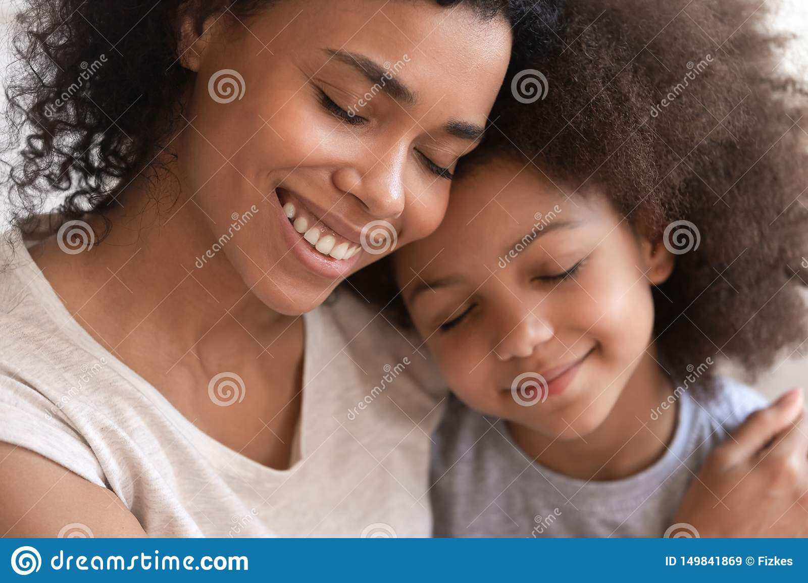 Loving young african mother holding embracing cute little kid daughter