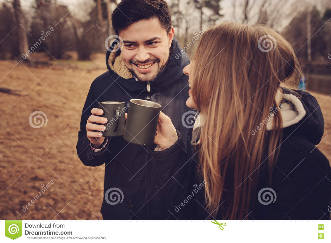 Loving young couple happy together outdoor, drinking tea from thermos, autumn camp