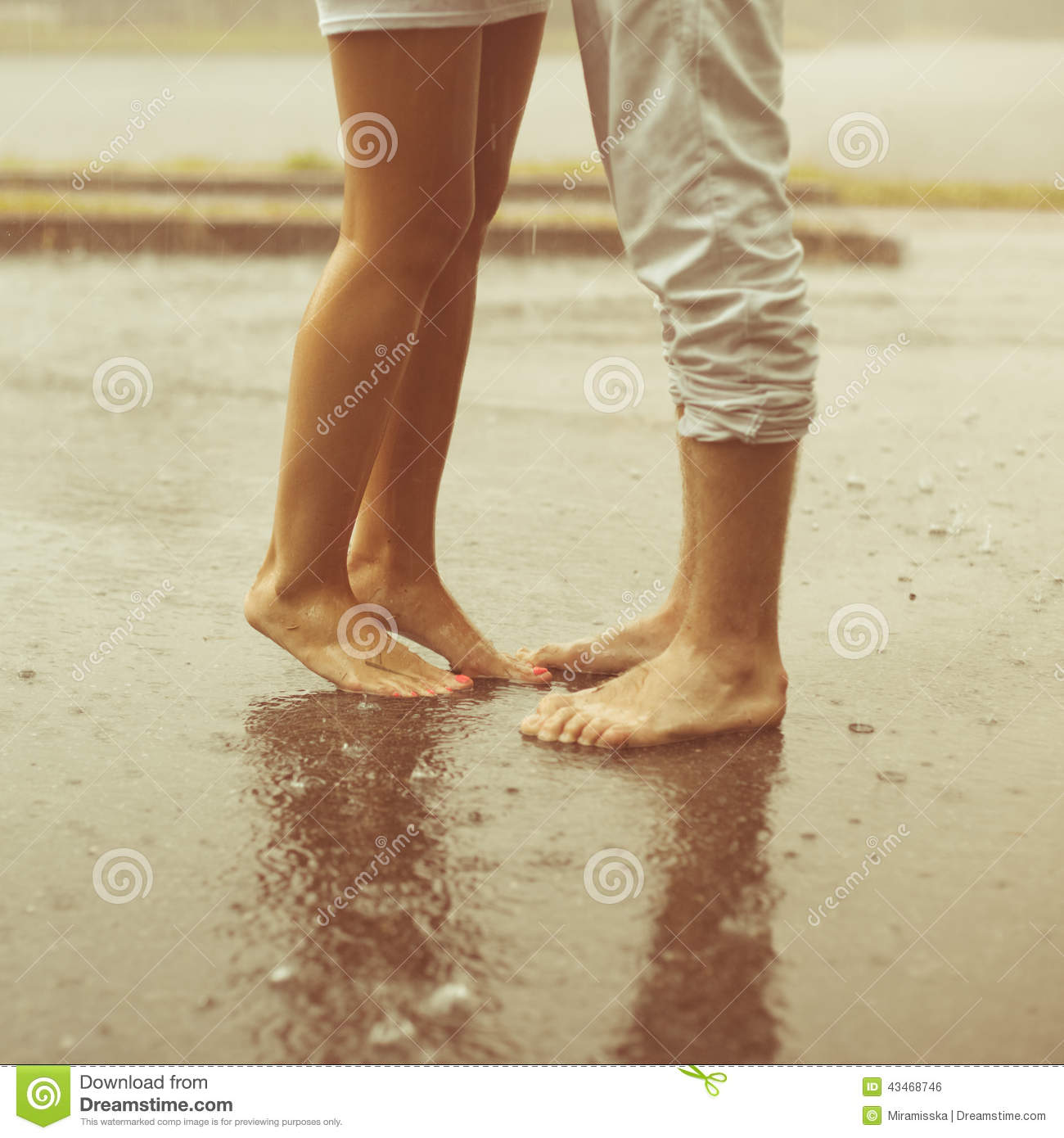 A loving young couple hugging and kissing under a rain. Lovers m