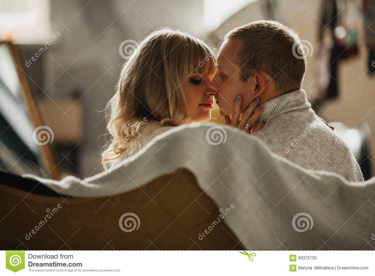 loving young couple kissing on the couch stock photo image 60372730. Black Bedroom Furniture Sets. Home Design Ideas