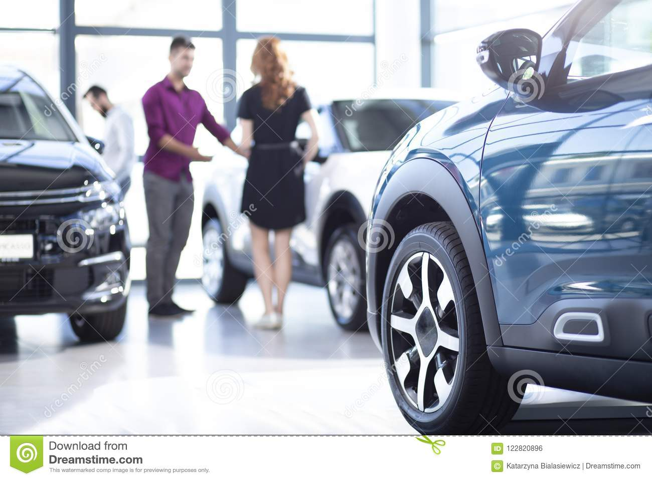 Low Angle Of Exclusive Car In A Dealing Salon With Seller And Buyer - Show low car dealers