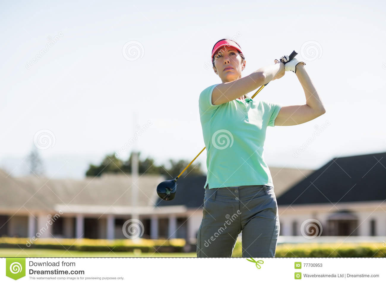 Low angle view of golfer woman taking shot