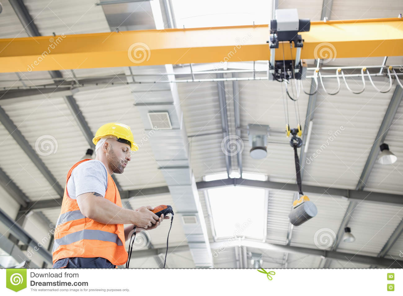 Low angle view of manual worker operating crane lifting steel in industry