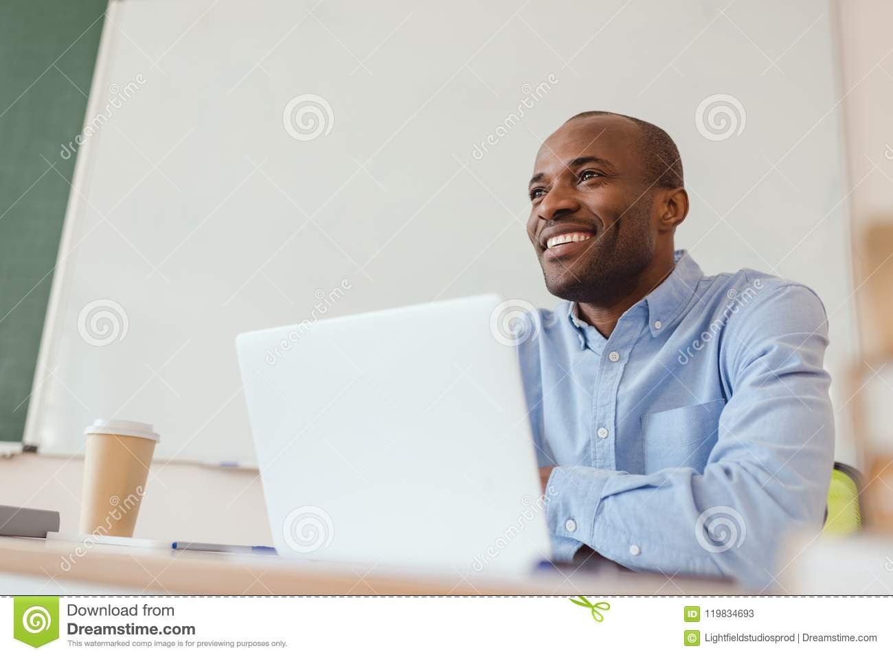 Low angle view of smiling african american teacher sitting at table with laptop
