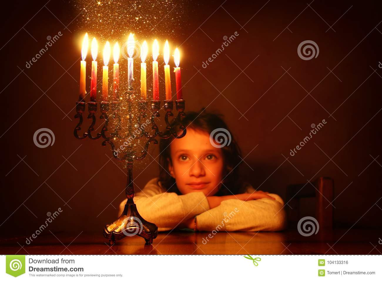 Low key image of jewish holiday Hanukkah background with cute girl looking at menorah & x28;traditional candelabra& x29;