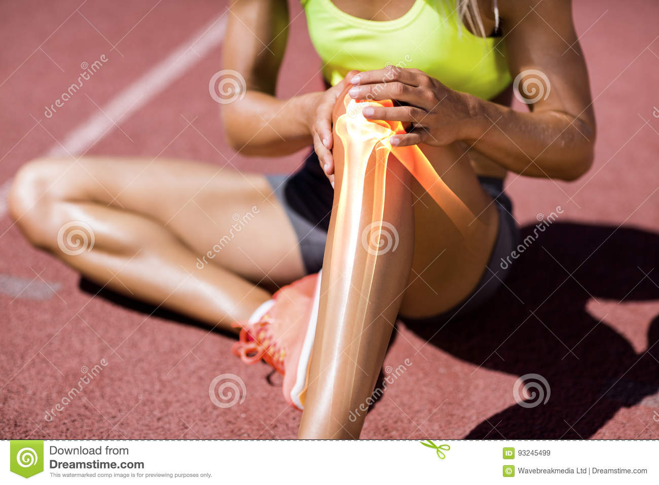 Low section of female athlete suffering from knee pain