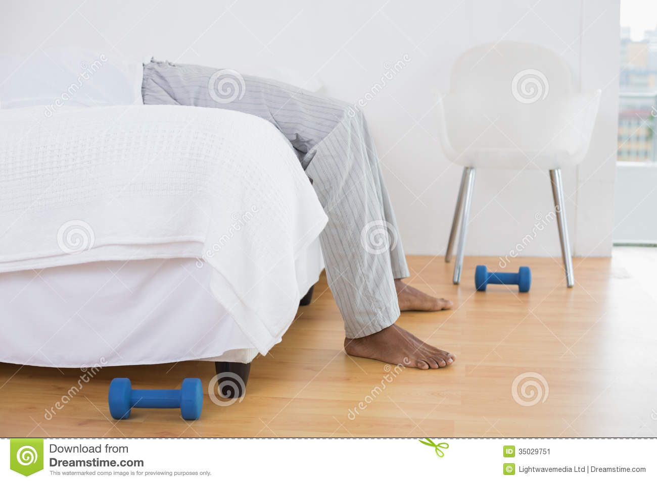 Low Section Of Man In Pajama Lying In Bed At Bright Home