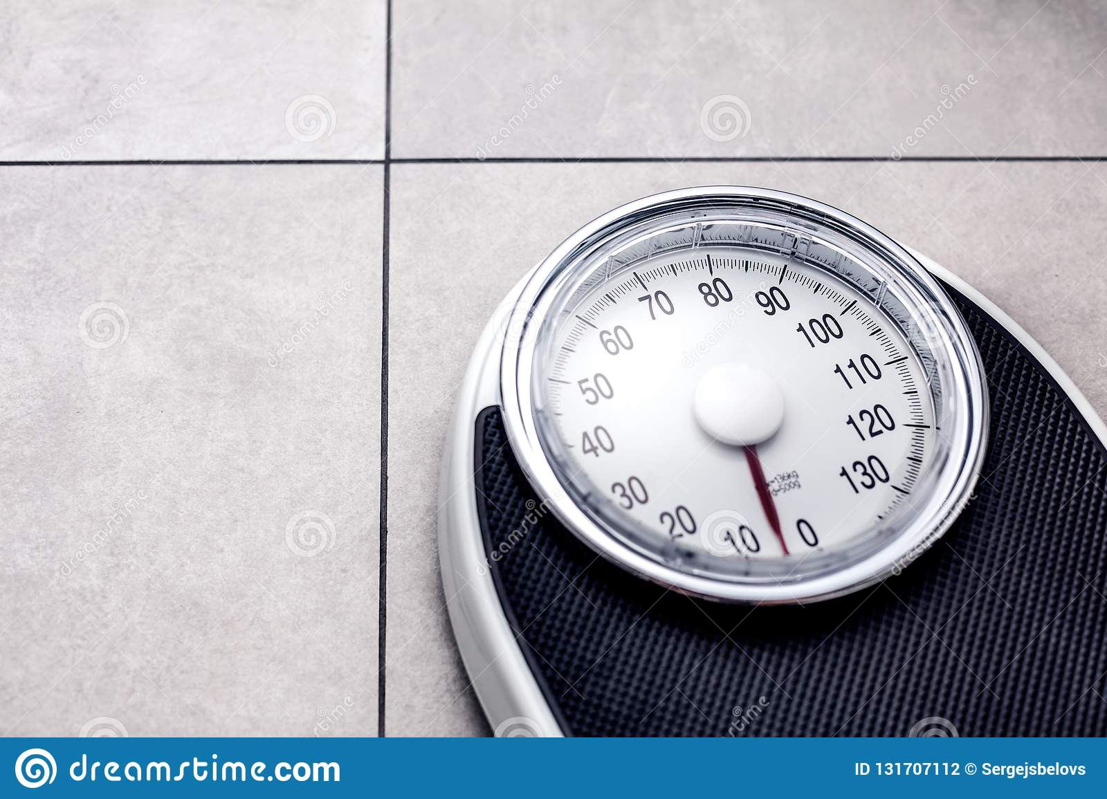 Low section of man standing on weight scale